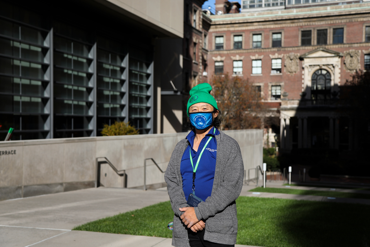A Barnard Health Ambassador with their mask and hat posted on Barnard's campus