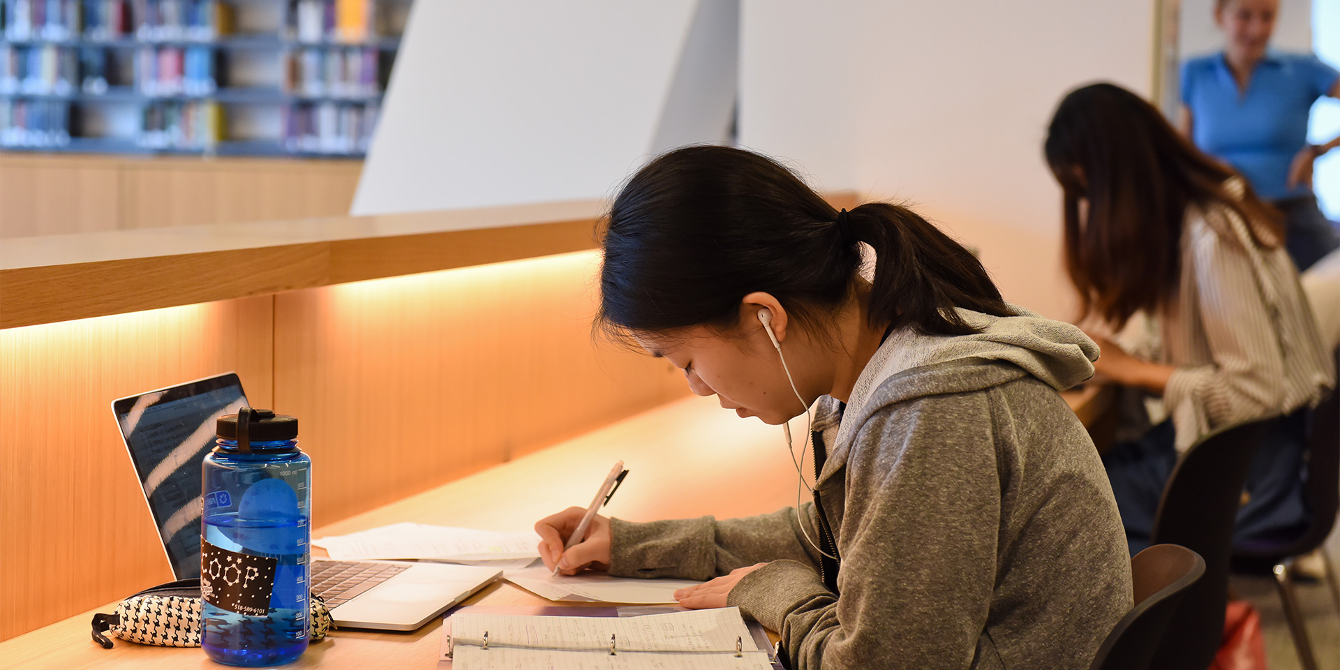 Student studying with laptop and earbuds